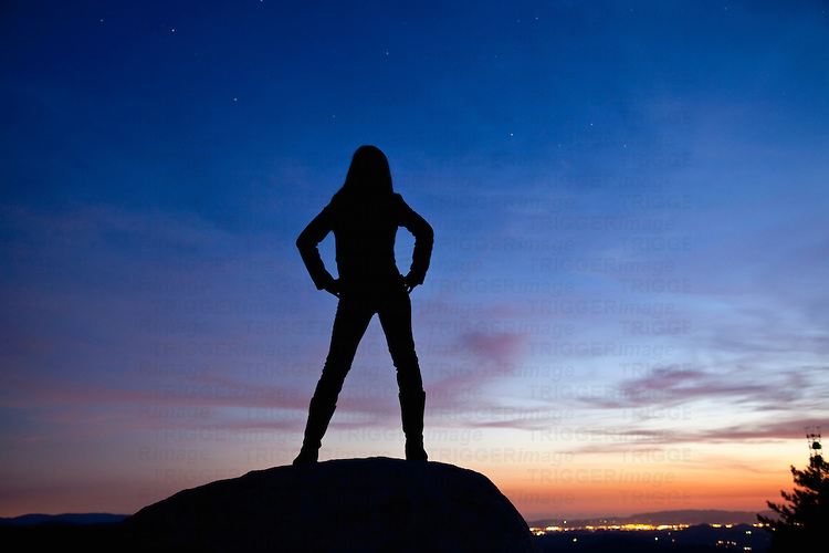 Silhouette of a woman standing on a rock at night overlooking th